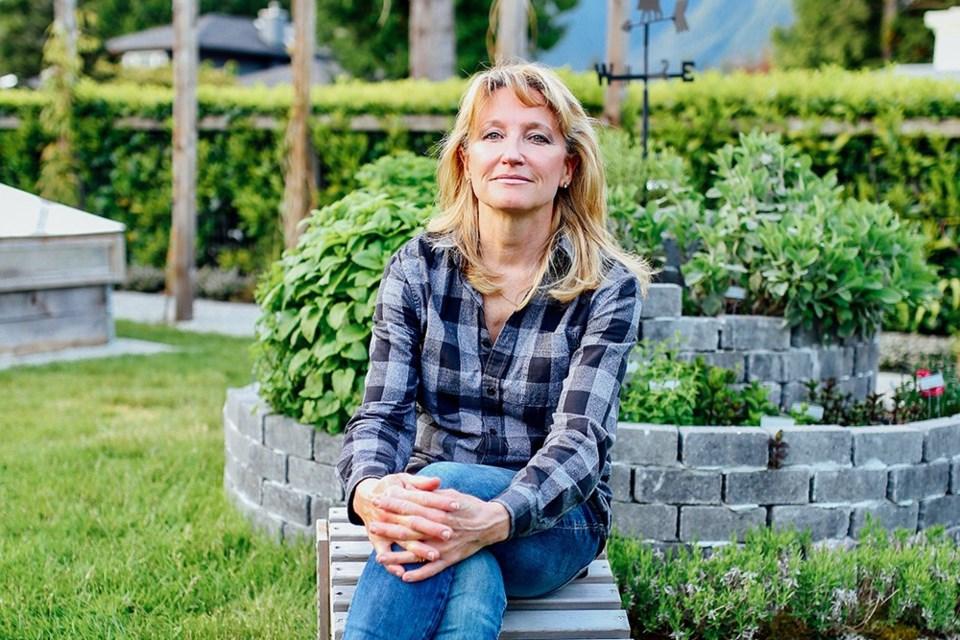 Urban  permaculture designer Laura Marie Neubert sits in her West Vancouver garden.