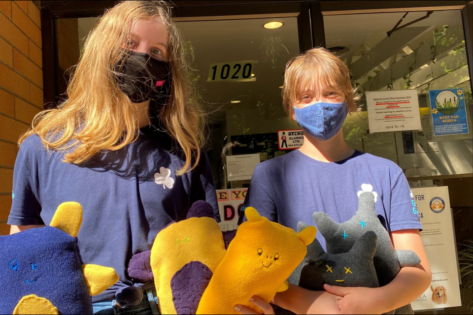 North Vancouver girl guides Georgia Chilton and Alice Link donate stuffed toys to BC SPCA West Vancouver branch for dogs to enjoy.