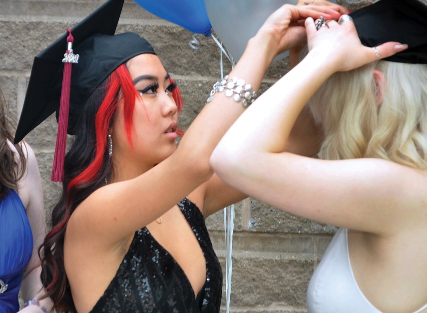Rockridge Secondary Grade 12 students Lili Goodwin and Rose Foy get prepped for graduation ceremonies May 31, 2021, at West Vancouver's Kay Meek Arts Centre.