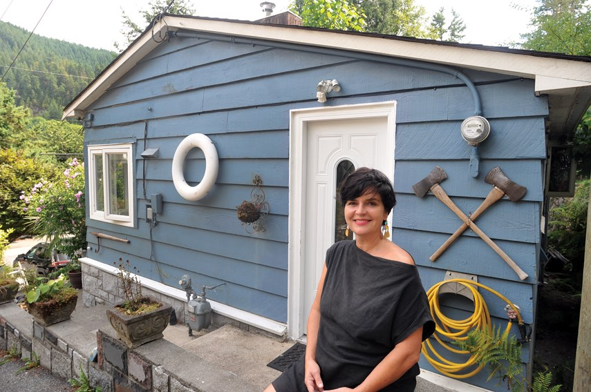 Heidi Woodley stands by her rented heritage cottage on Nelson Avenue in West Vancouver's Horseshoe Bay, one of eight such cottages across three lots. Woodley and others have started the Horseshoe Bay Cottagers' Collective to attempt to purchase the properties through a co-ownership structure.