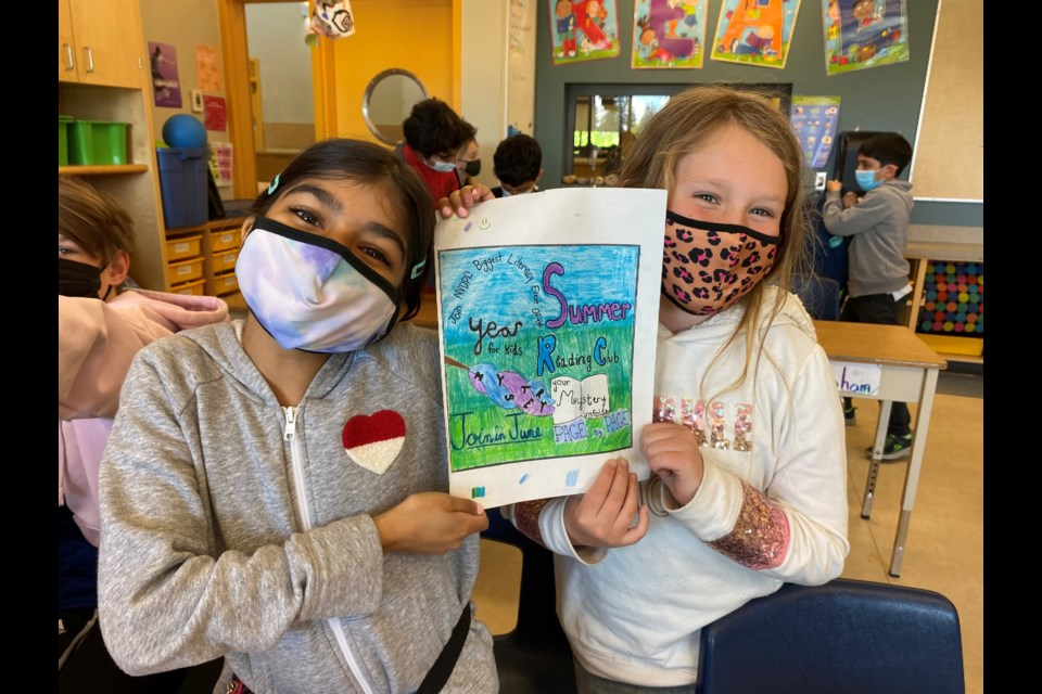 Highlands Elementary Grade 5 students  Jenna Pardhan and Josie Dalrymple with the one of the pieces they put together for the Kids Design Your Ads project.