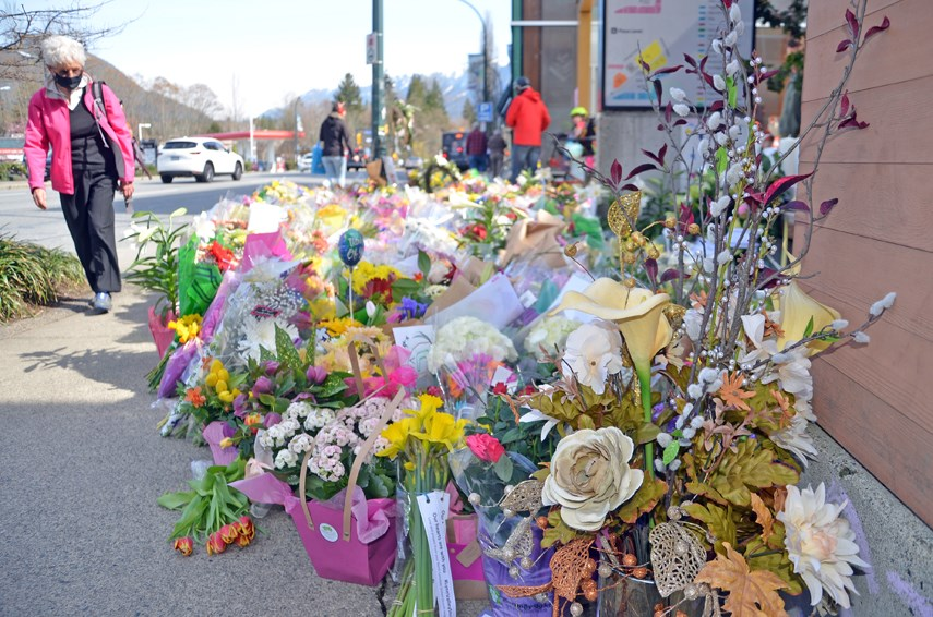 Hundreds of flowers line the sidewalk outside the Lynn Valley Village library complex. On Wednesday, March 31, the library reopened four days after a multi-victim stabbing that left one woman dead and sent six people to hospital.