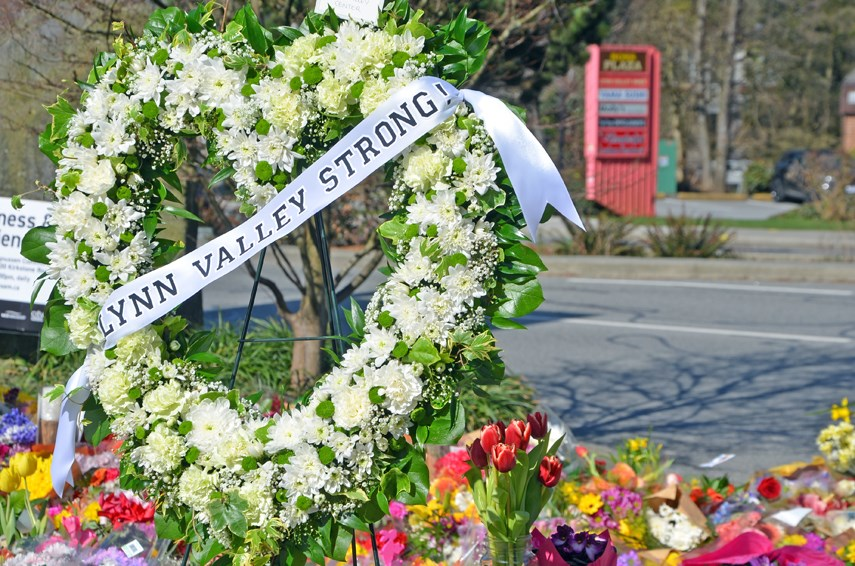 Hundreds of flowers, bouquets and memorials blanket the sidewalk at Lynn Valley Village library complex. On Saturday, April 3, a candlelight vigil is planned, one week after a stabbing rampage in the community.
