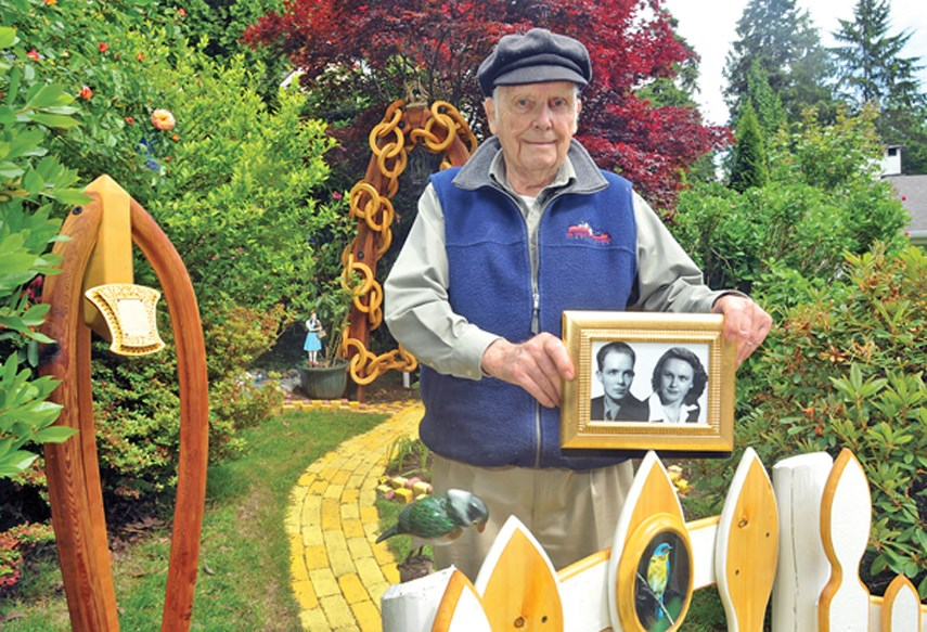 North Vancouver resident Ed Lien holds up a portrait of himself and his late wife Shirley with his Land of Oz display in the background at his Lynn Valley home on May 31, 2021.