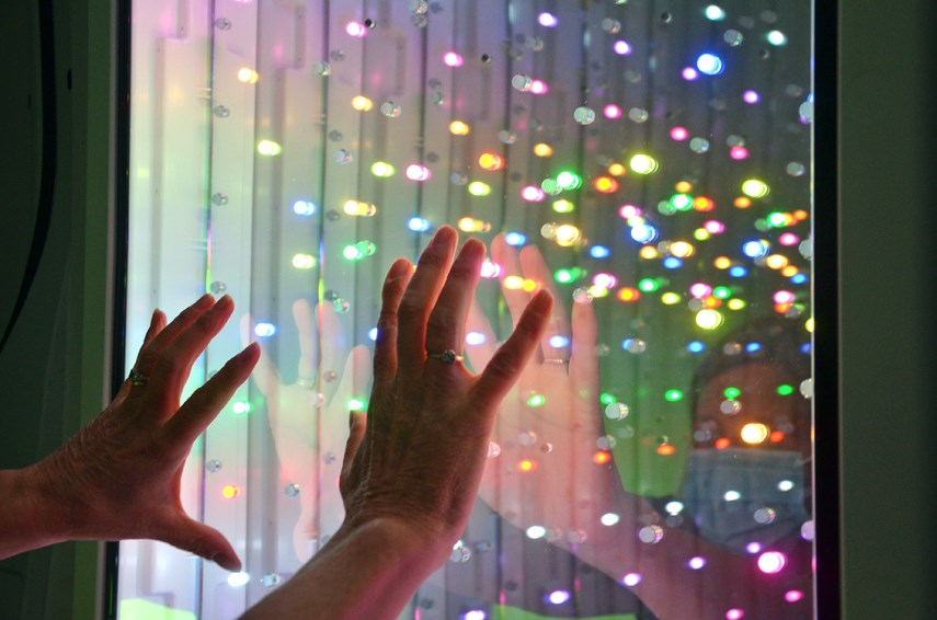 A user tests out a mirrored panel, full of bright LEDs that appear as if they're stretching out into infinity, part of North Shore Disability Resource Centre's new mobile Snoezelen room.