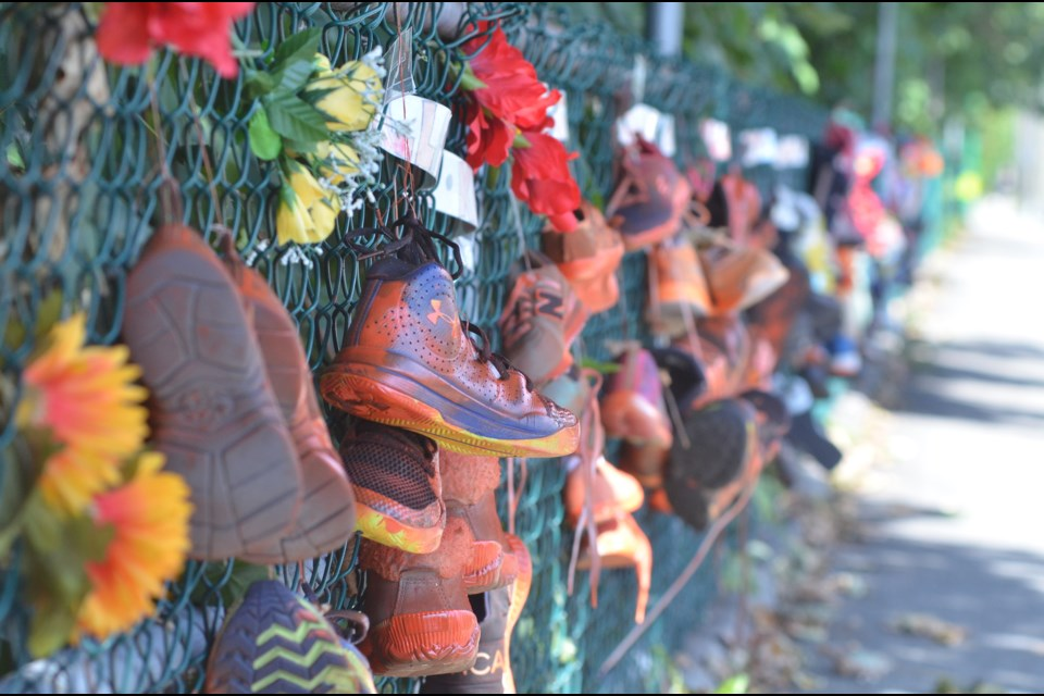 Orange shoes line a chain-link fence adjacent to the sidewalk on the north side of Lynn Valley Road, just east of Pioneer Square, created by Gwynneth Powell Sobejko with the help of the community.