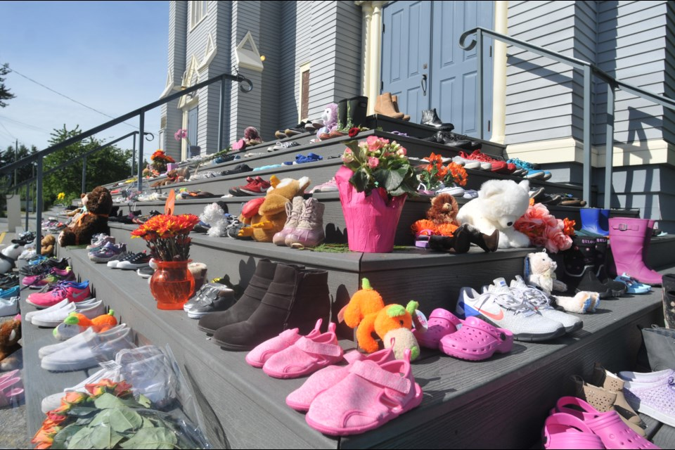 Dozens of children's shoes line the stairs of St. Paul's Church in the Squamish Nation community of Eslhá7an, Mission reserve, on Monday, May 31, 2021, in honour of the children buried at Kamloops Residential School.