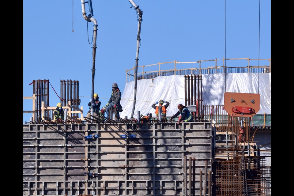 Workers pour concrete into forms on the site of the massive new sewage treatment plant construction project in North Vancouver in March 2021.