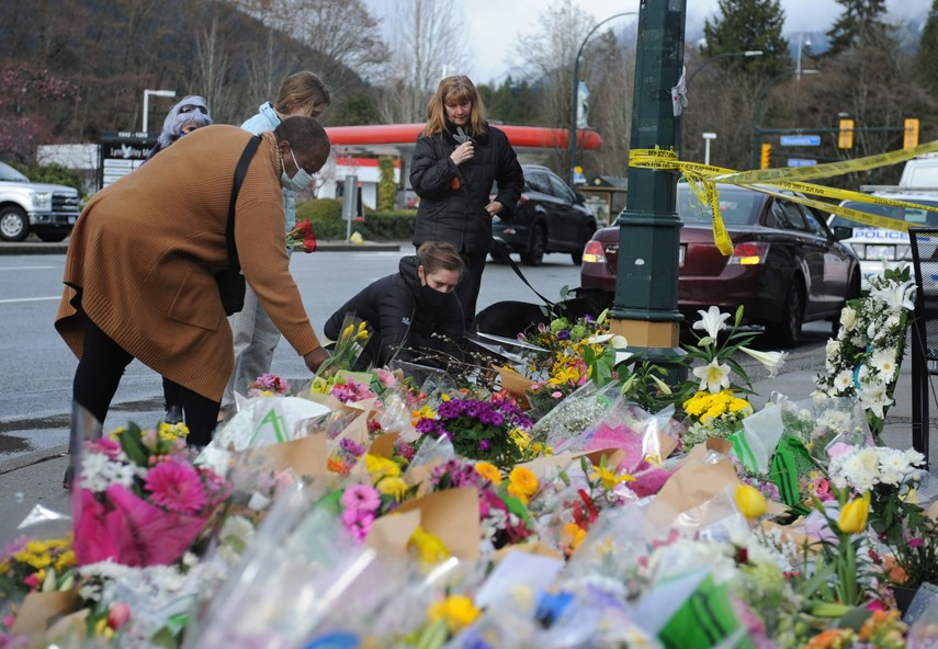Residents lay cards and flowers on a quickly growing memorial outside the Lynn Valley Library complex Sunday, March 28, one day after a man killed one person and injured six others in a knife attack.