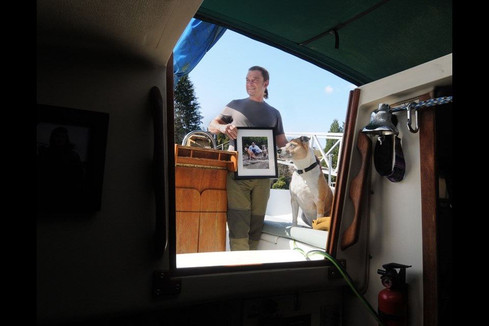 Matthew Witt and Rio on their family sailboat in North Vancouver. Matthew holds a photo of his son Sebastian, who died in 2015 of a fentanyl overdose.