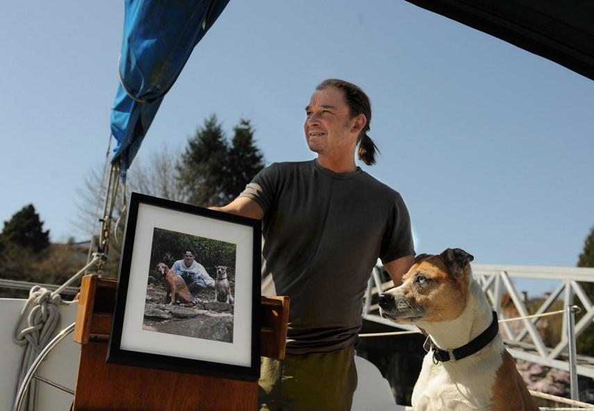 Matthew Witt and Rio on their family sailboat. Matthew holds a photo of his son Sebastian, who died after taking a toxic supply of fentanyl at age 20, on May 18, 2015.