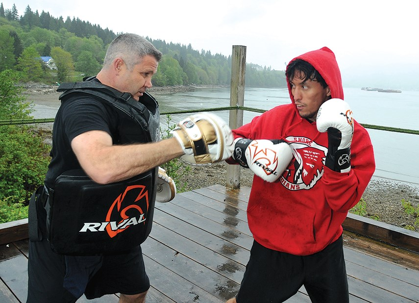 Former Canadian Olympic boxer Manny Sobral coaches boxer Jacob George at a waterfront boxing ring on Tsleil-Waututh Nation lands. George recently scored a first-round TKO in his professional boxing debut.