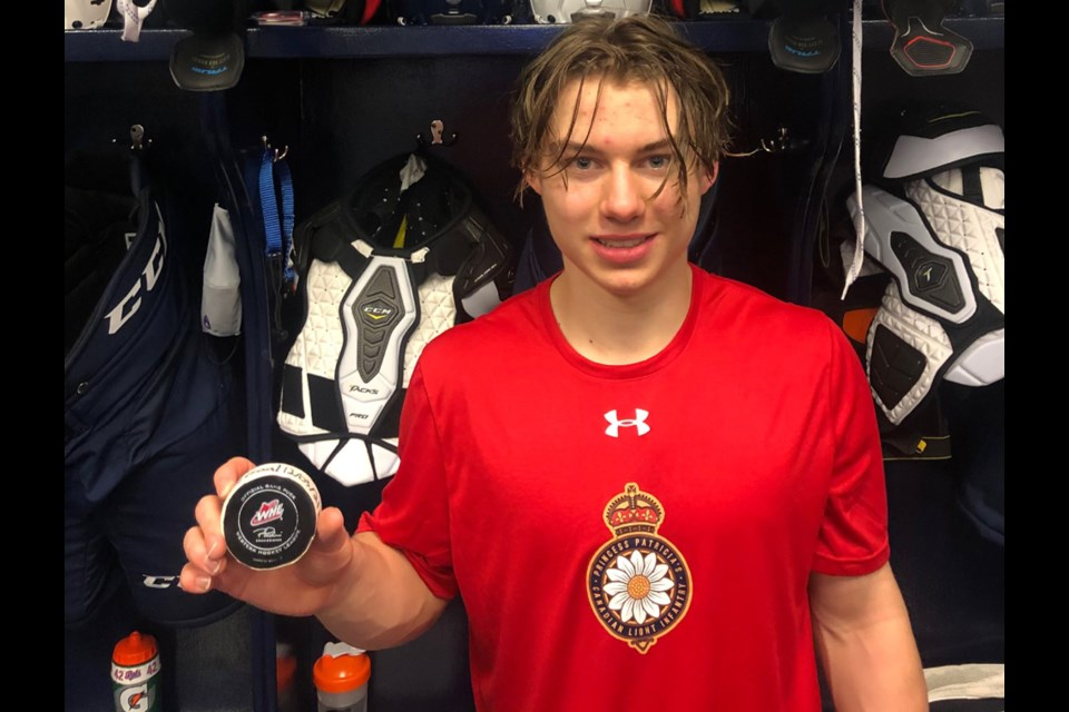 "Connor Bedard of the Regina Pats shows off the puck he fired in for his first WHL goal in his first WHL game, March 12, 2021 against the Prince Albert Raiders. The North Vancouver native, the first player in league history to earn ""exceptional status"" early entry, scored twice in his WHL debut."