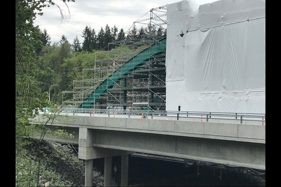 North Vancouver's old Highway 1 Lynn Creek Bridge is emerging from its protective cover in Lions Gate green. May 6, 2021.