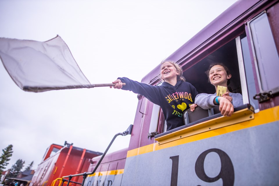Aileen Maher waves a signalling flag out of a locomotive with her sister Madeline at the Champion Park open house on Aug. 10. (BRENT CALVER/Western Wheel)