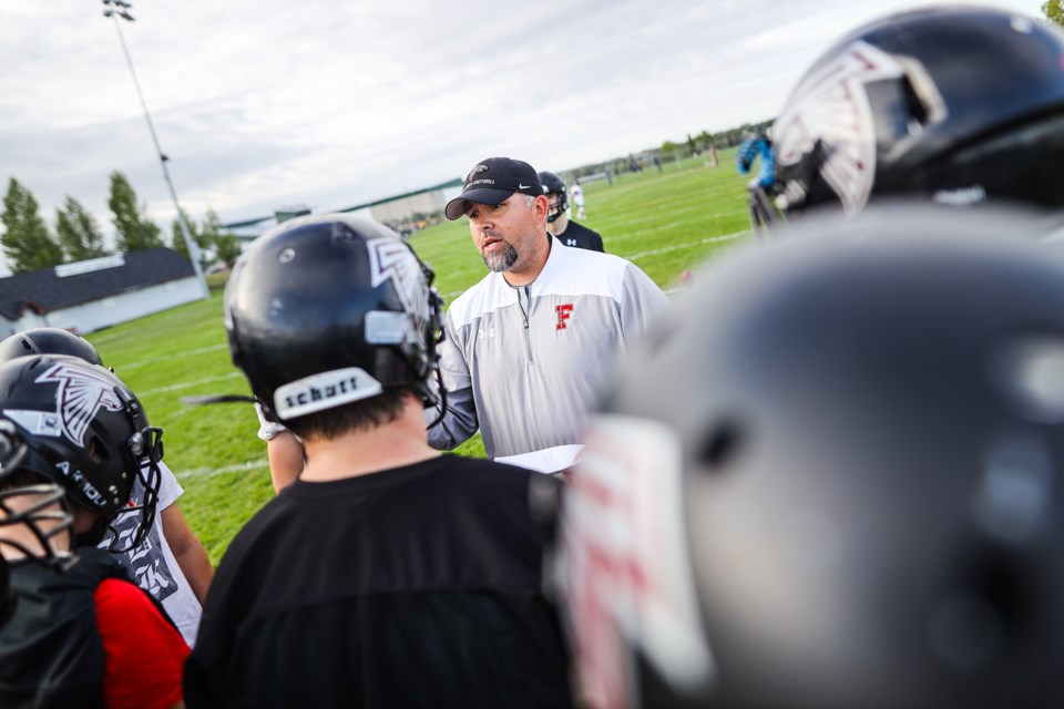 The Foothills Falcons new head coach Nathan St. Dennis runs the team through drills in practice on Aug. 29. (BRENT CALVER/Western Wheel)