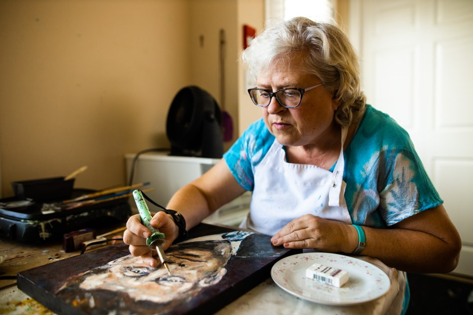 Penny Gunderson works on encaustic artwork in her home on Aug. 29. Gunderson, who suffers from autoimmune diseases and mental health issues, was selected to be a part of that SPARK Disability Art Festival in Calgary.  (BRENT CALVER/Western Wheel)