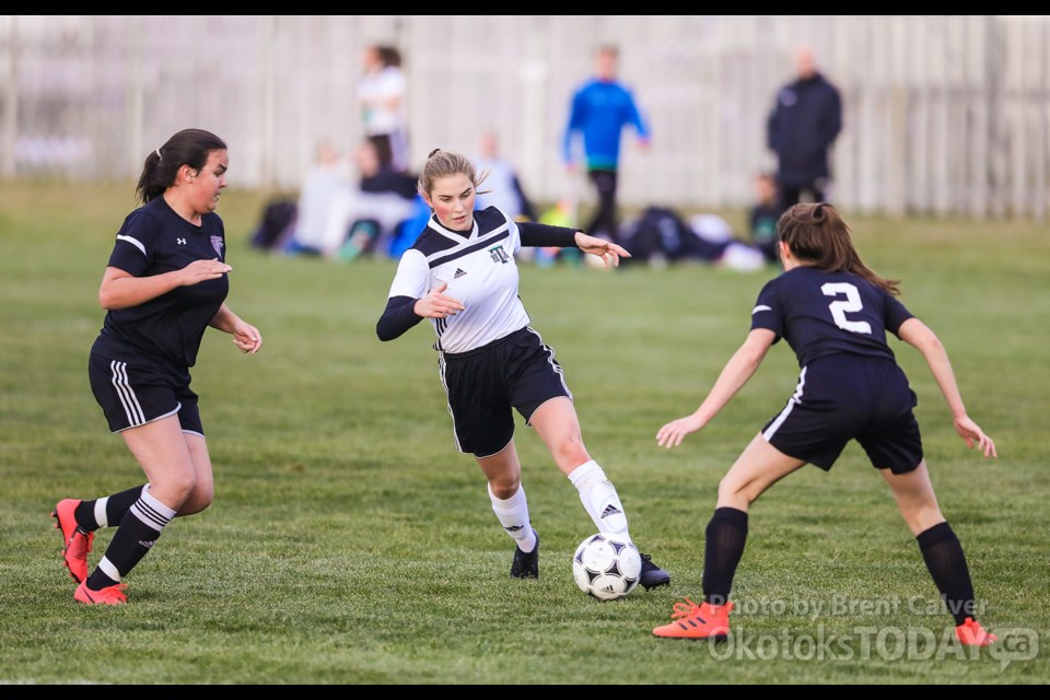 Holy Trinity Academy Knight Brielle Masse dribbles between Falcons Meghan Dhaliwal and Kate Kennedy in the FAC girls soccer final Oct. 15 at Riverside Park. (BRENT CALVER/Western Wheel)