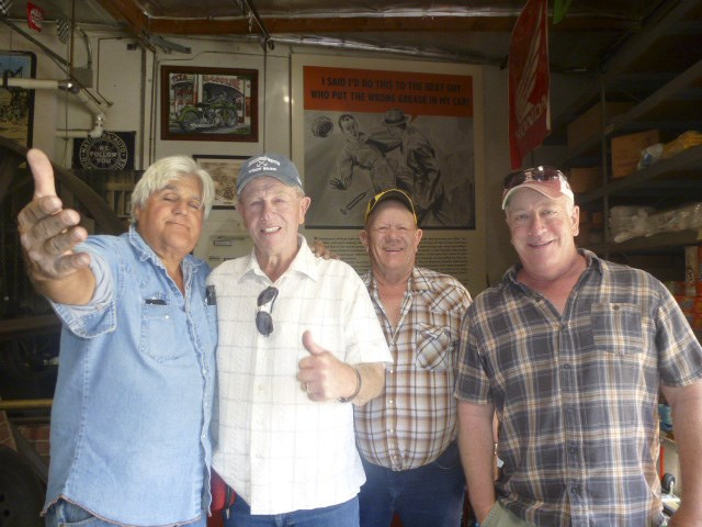 From left: Jay Leno takes a break in his garage to meet Robert Carr, his cousin Dale Carr and son Kevin Carr during their tour of Leno's garages in Burbank, CA.