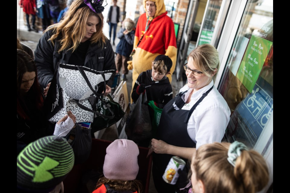 """Sobeys manager Jaclyn Geddie greets students from Westmount School to receive donations on Oct. 31 at a """"Reverse Trick or Treat"""" event. Students and teachers from the school went out in costume to deliver food to Okotoks Food Bank donation points on Halloween. (BRENT CALVER/Western Wheel)"""
