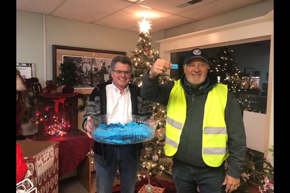 Don Moss, president of Kiwanis Club of Okotoks, draws the winning ticket during Light Up Okotoks on Nov. 15 with Western Wheel publisher Shaun Jessome.