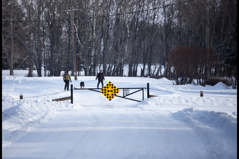 A couple walks their dog along Imperial Drive east of Royalite Way on Jan. 9. Turner Valley town council passed second reading on Jan. 6 to close the road to pedestrian traffic. Once third reading is passed, ownership of the land the road is on will be transferred to the golf course. (Brent Calver/Western Wheel)