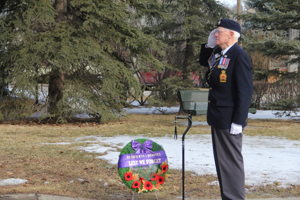 Malcolm Hughes, chairman of the Royal Canadian Legion Branch #291 Okotoks, salutes the Canadian flag during the playing of the national anthem at a Birth of the Nation Day ceremony to commemorate the Battle of Vimy Ridge on April 9. (Krista Conrad/Western Wheel)