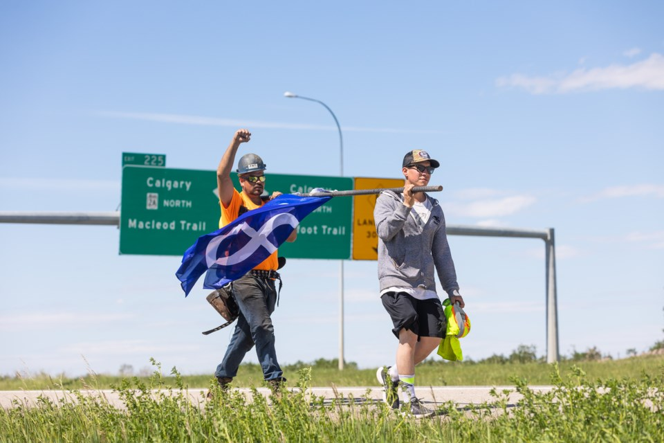 Indigenous men Dan Boudreau (yellow shirt) and friend Stefan Campbell walk down Highway 2 north of Okotoks with the Métis flag on a 100-pound piece of rebar on June 13. The two men (Boudreau a Métis and Campbell a status Indian) walked approximately 40km from Calgary to the site of the Dunbow (also known as St. Joseph's) Industrial School to raise awareness for indigenous children who suffered in Canada's residential school system.