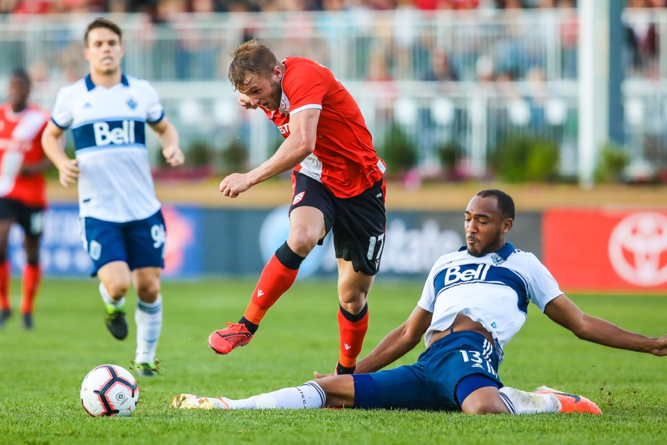 Cavalry FC attacker Nico Pasquotti's shot on net is blocked off by Vancouver Whitecaps defender Derek Cornelius in the third round game of the Canadian Championship at Spruce Meadows on July 10. (BRENT CALVER/Western Wheel)