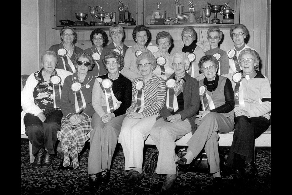 Founding members of the Okotoks Ladies' Curling Club celebrating the 25th anniversary of the club in 1982. Back row: Louise Holmes, Hazel Snodgrass, Evelyn Johnson, Jean Milligan, Chris Poffenroth, Chris Aikens, Lucille Cole and Dot Jesperson. Front row: Mary Wild, Winnie Carr, Audrey Hoiland, Jean Packenham, Myrtle MacDonald, Margaret Aggett and Kay Christensen. (Photo courtest of the Okotoks Museum & Archives)