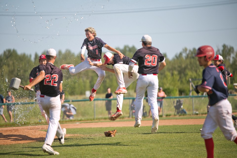 Okotoks Dawgs 15U Black's Deri Steiert-Couture and Karter Andersen celebrate the team's 12-3 win in the 15U AAA provincial final, Aug. 4 at Conrad Field. (Remy Greer/Western Wheel)