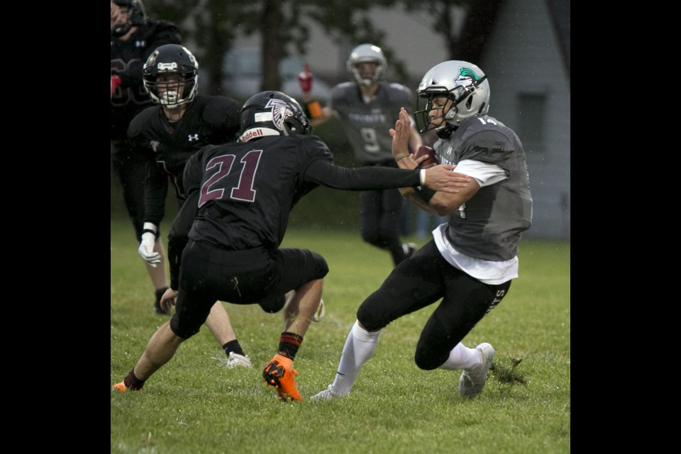 Holy Trinity Academy slotback Noah Gutek tries to work his way around Falcons defensive back Jamison Strilchuk on Sept. 20 at the Comp. (Bruce Campbell/Western Wheel)