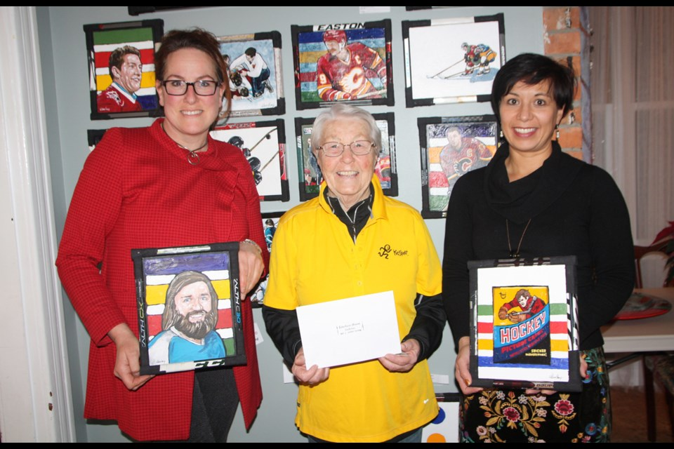LIneham House Galleries owner Cheryl Taylor, left and Janifer Calvez of Lineham present a $500 cheque to KidSport Okotoks representative Marg Cox in December. The funds came from the sale of a hockey painting done by Timothy Wilson Hoey.
