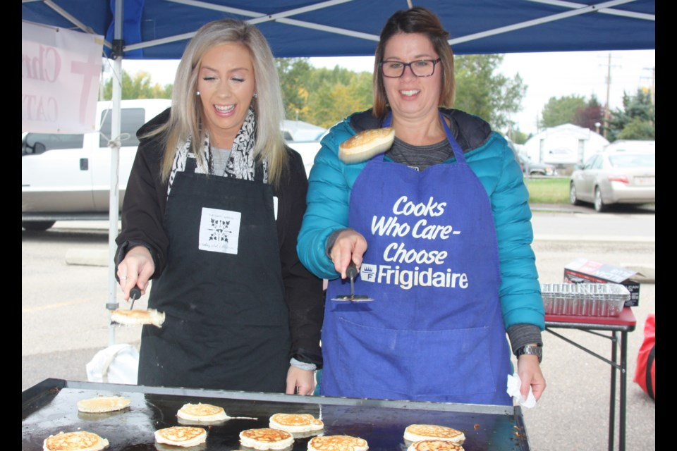 Lindsay Fagan and Janell Ferris from Christ the Redeemer Catholic Schools flip some flapjacks at the school division You're Awesome appreciation breakfast on Sept. 20.