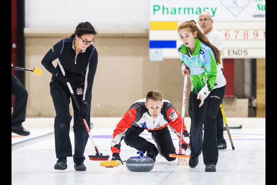 Chantal Marleau, left, and Macey Anderson prepare to sweep Marc Kennedy's rock at the Oilfields Curling Club on Oct. 18. (BRENT CALVER/Western Wheel)