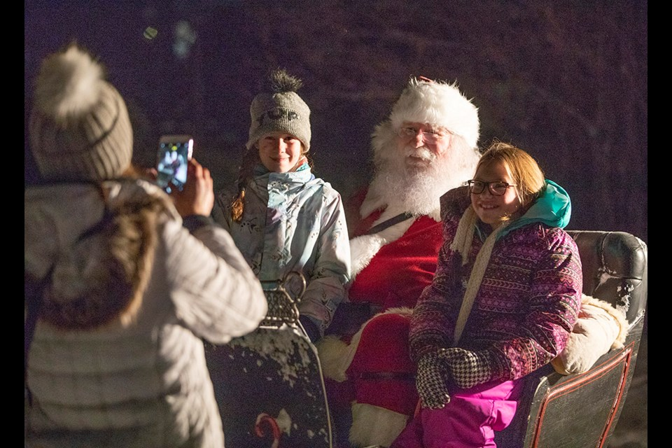 Nicole Rarick snaps a photo of her daughter Sutton Rarick, left, and friend Cassie Borgford with Santa Claus during Light Up Okotoks in 2018. (Wheel File Photo)