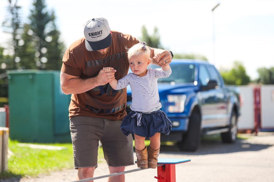 Willow Toews is helped across a tightrope at the Spectacle Blue stand by her dad Dave during the Teddy Bear Picnic at the Okotoks Recreation Centre on July 11. Donations were accepted on behalf of the Okotoks Family Resource Centre's Emergency Fund. (BRENT CALVER/Western Wheel)