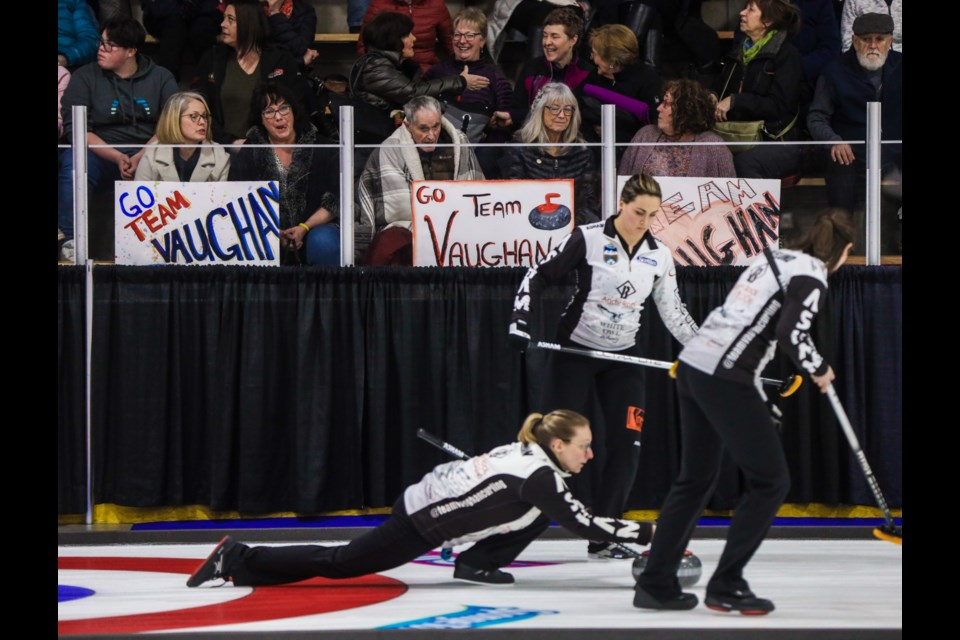 Team Vaughan skip Jodi Vaughan throws past a group of fans sporting signs during draw 5 of the 2020 Alberta Scotties at Murray Arena in Okotoks on Jan. 24. (Brent Calver/Western Wheel)