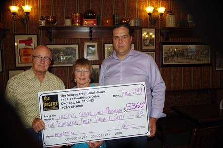 The George Traditional House's John Nicastro, right, presents a $5,360 cheque to Brian and Shannon Olson of the Okotoks United Church School Lunch program on June 28. The funds were raised from The George's annual golf tournament at Turner Valley Golf Course on June 1. (photo submitted)