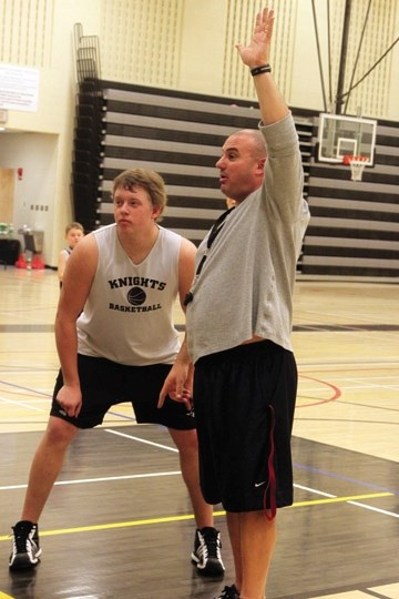 Holy Trinity Academy coach Sam Aiello instructs a drill with post Alex Lorenz during a December practice. HTA will play host to the annual Knights Classic Tournament on Jan.