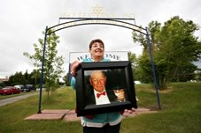 Maureen Parsons holds a photo of her father Bob Lochhead in front of the former Centennial Campground in Black Diamond, which was renamed Bob Lochhead Memorial Park in his