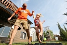 Turner Valley resident Merv Page and his three-year-old granddaughter Amelia Myles jump through a sprinkler in his backyard. The Towns of Black Diamond and Turner Valley