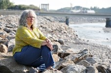 Turner Valley resident Roxanne Walsh sits beside the Sheep River in Turner Valley. She launched an appeal of the town' s water treatment plant to get documentation