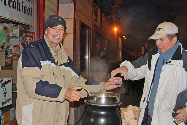 Black Diamond Bakery and Coffee Shop' s George Nielson serves up chili to Calgarian Ron Isbister during Light Up Black Diamond in 2012. This year' s event takes