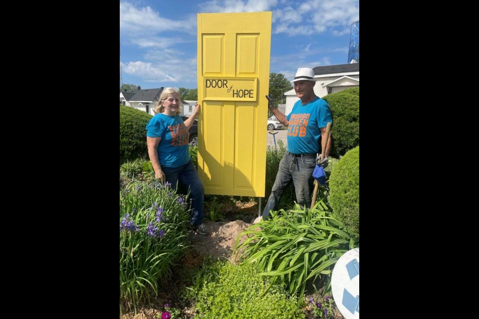 Washago Garden Club President Don Westcott and Secretary Cathy Westcott stand with the 'Door of Hope'.