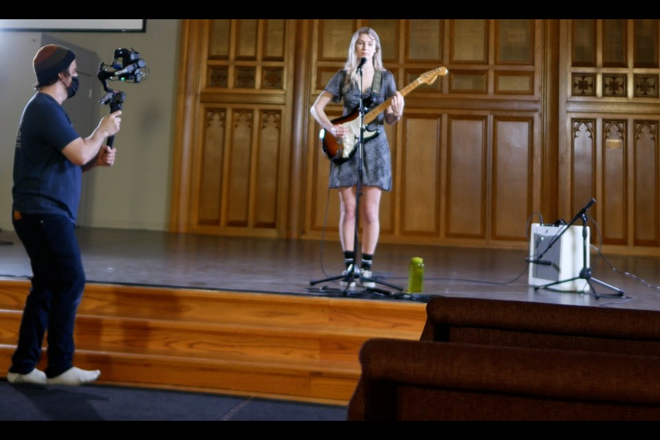 Local musician Sam Johnston is shown performing at St. Paul's for the virtual Roots North Music festival. She is being filmed by Tyler Knight of Knightvision Media.
