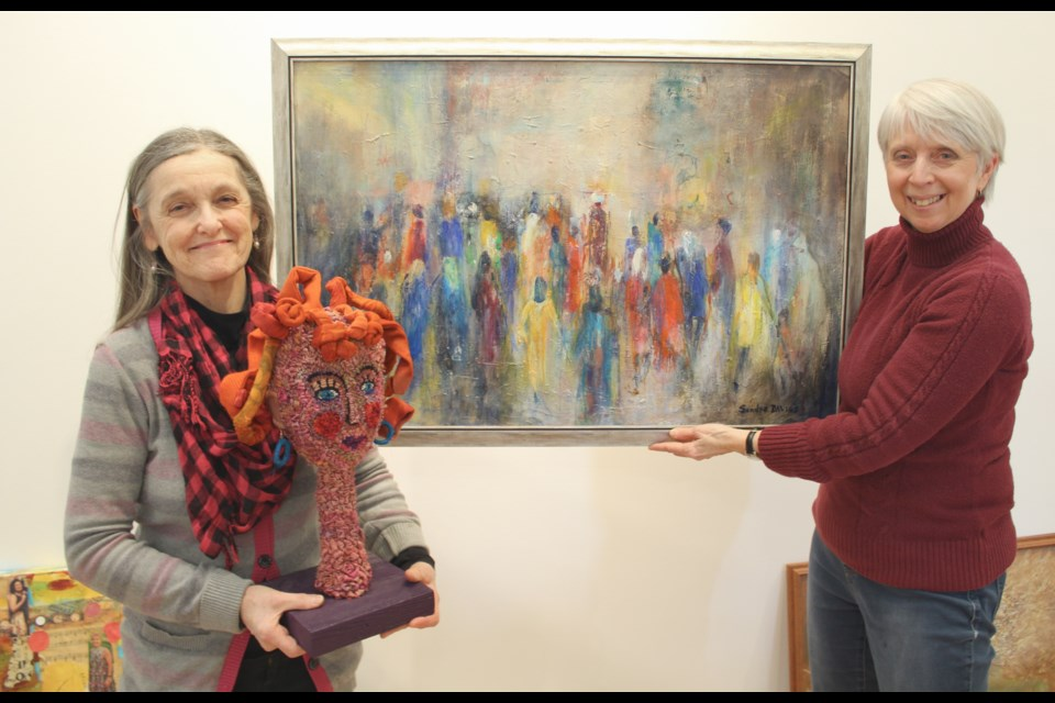Mary Ann Tully, left, and Juliana Hawke show off a couple of the pieces that will be featured in the International Women's Day Art Show, which opens Feb. 16 at the Orillia Museum of Art and History. Nathan Taylor/OrilliaMatters