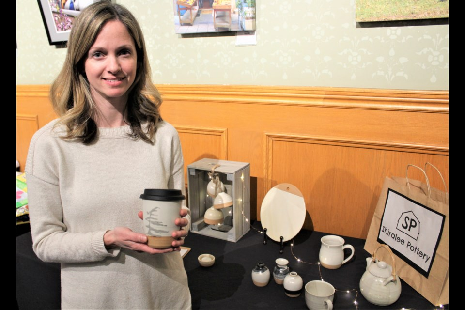 Danielle Skentzos, owner of Shiralee Pottery, shows off one of her travel mugs Thursday during the Artrepreneur Expo at the Orillia Opera House. Nathan Taylor/OrilliaMatters