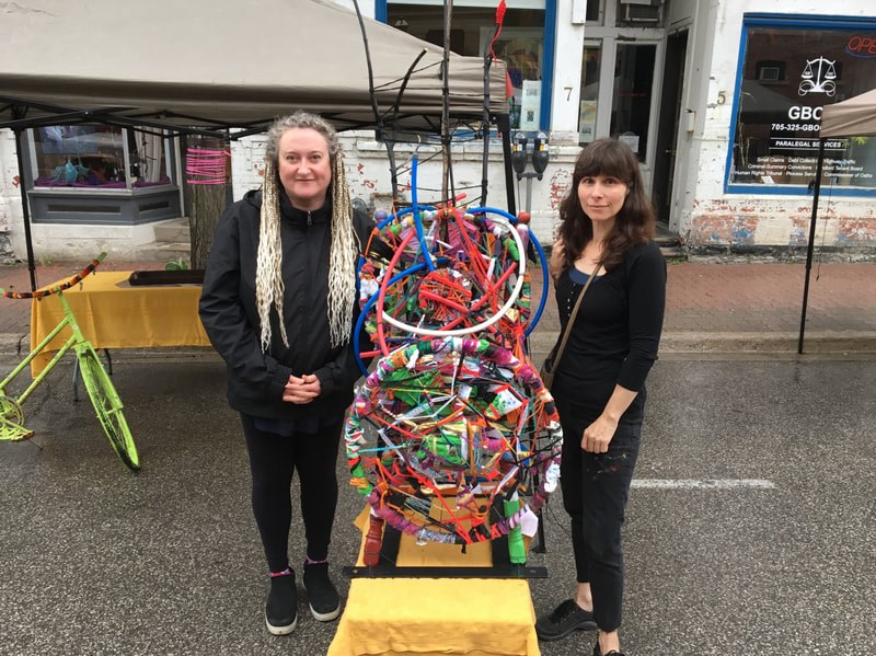Local artists Sylvia Tesori and Patti Agapi in simpler times, with a collaborative piece in the Peter Street Arts District. credit Patti Agapi