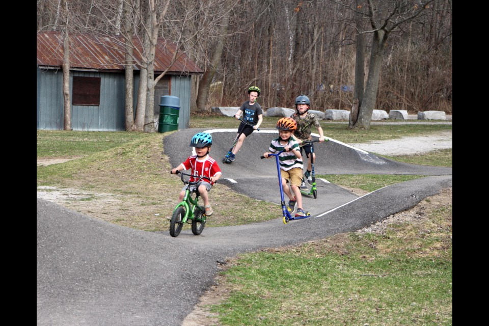 Two sets of brothers, Henry and Morley Peacock in the foreground, and Lochlen and Liam Rogers, following, can spend hours speeding around the pump track at Centennial Park in Washago.